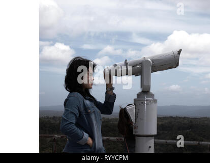 Young Filipina standing on the lookout area overlooking the Chocolate Hills in Bohol Philippines - Stock Photo