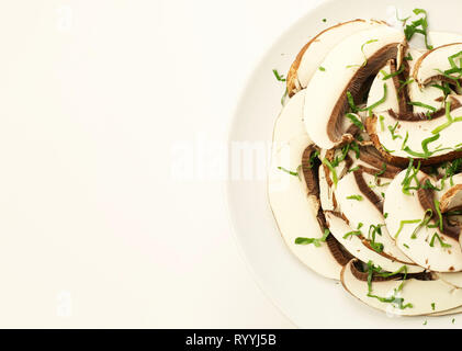 Sliced fresh raw Portobello mushrooms in a white plate - Stock Photo