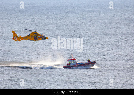 a helicopter of the dutch coastgard is abseiling a man over the sea during a rescue drill - Stock Photo