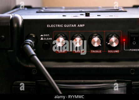 Guitar amplifier with dials and controls for volume, gain, bass, treble. Jack cable connected. Black amp with red light on. - Stock Photo