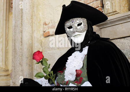 Man with red rose dressed in traditional mask and costume for Venice Carnival standing at Doge's Palace, Piazza San Marco, Venice, Veneto, Italy - Stock Photo