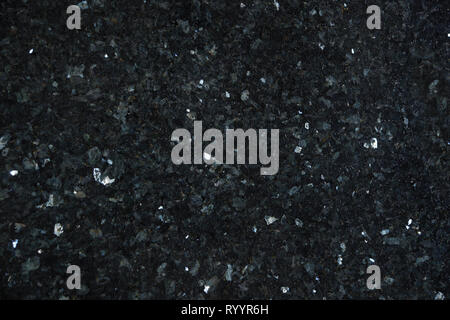 Natural granite of dark color with bright glitters on the surface, called Emerald Pearl. - Stock Photo