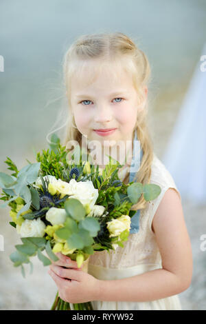 Adorable little bridesmaid holding beautiful flower bouquets after wedding cemerony outdoors. Destination wedding on Cephalonia island on Greece. - Stock Photo