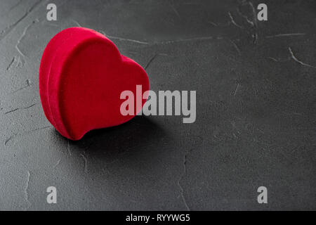 Red box for rings in the shape of a heart on a concrete background - Stock Photo