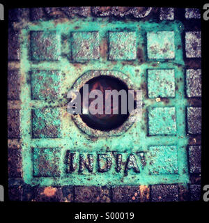 Looking down at an Indian drain cover - Stock Photo