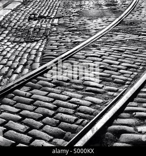 Old cobblestoned street with historic train tracks showing in the DUMBO neighborhood of Brooklyn, New York. - Stock Photo