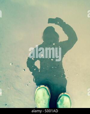 Selfie, reflection of person with green rubber boots - Stock Photo