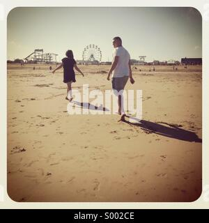Lovers walking on beach - Stock Photo