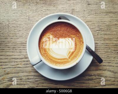 Heart shaped coffee art on a latte - Stock Photo