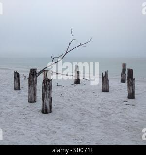 Old dock/ jetty in mist on Fort Myers Beach, Florida, USA - Stock Photo