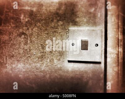 Old dirty light switch turned on - Stock Photo