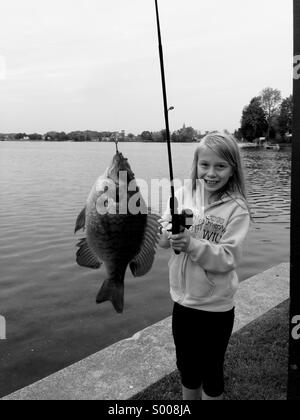 A young girl smiles after catching a fish. - Stock Photo