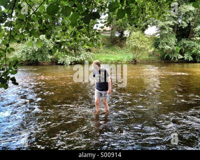 Young teenage Boy wading in fresh water stream river - Stock Photo