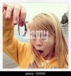 A girl's eyes light up while looking at a squirmy crawly worn. - Stock Photo