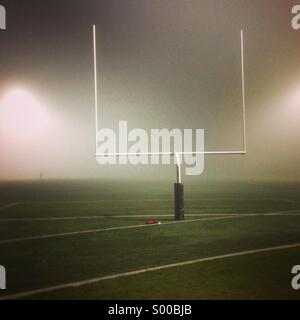 Football field and goal post enveloped in fog at night - Stock Photo