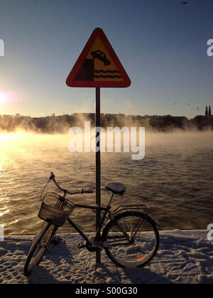 Bicycle leans against dock edge sign in central Stockholm with misty lake at dawn in background. - Stock Photo