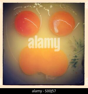 Broken eggs yolk face. Faces in objects - Stock Photo