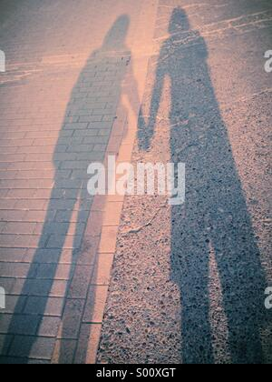 Long shadow of a couple holding hands with a pink cast - Stock Photo