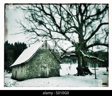 Small stone chapel at Mas Saint-Jean on snowy winter day, Saint-Sulpice-le-Dunois, La Creuse, Limousin, France - Stock Photo