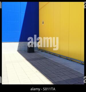 A large shadow being cast on the side of the Adelaide IKEA building, engulfing a rubbish bin. - Stock Photo