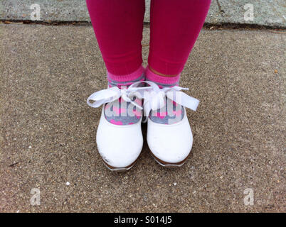 Little girl in white tap dancing shoes with bows and heart socks - Stock Photo