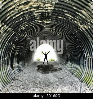 Woman arms stretched out in corregated metal tunnel. - Stock Photo