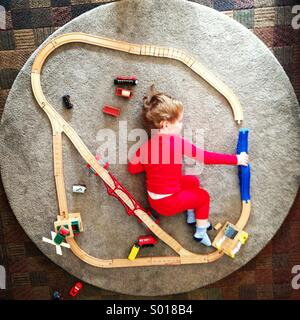 Little boy playing with a toy train track - Stock Photo