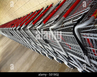 A long line of shopping carts create an interesting perspective - Stock Photo