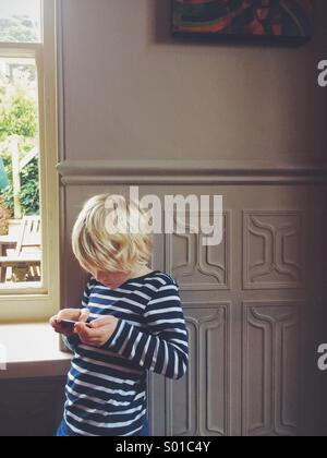 A young boy playing on an iPod - Stock Photo