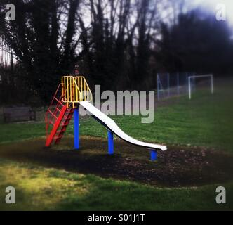 Children's slide in empty playground - Stock Photo
