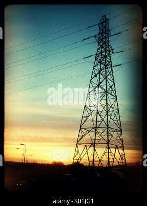 Electricity pylon tower at sunset - Stock Photo