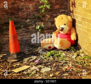 Abandoned teddy bear amongst rubbish near a traffic cone - Stock Photo