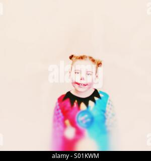 Young girl dressed as a clown with hair in buns. Colourful against a plain background - Stock Photo