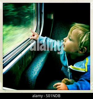 Young boy looking out of a train window, UK - Stock Photo