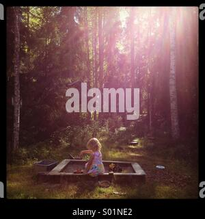 A young girl playing in a sandbox in a dreamlike sun drenched forest - Stock Photo