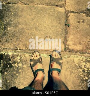 My own two sandalled feet exploring a ruined temple of Cambodia's Khmer Kings - Stock Photo