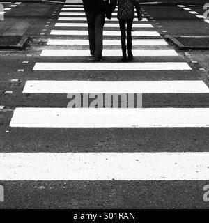 Two people on zebra crossing - Stock Photo