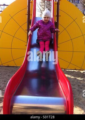 Child on playground sliding - Stock Photo