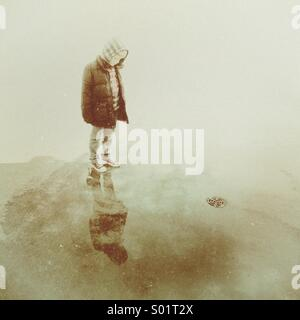 Young boy stood in a puddle looking at his reflection before the water goes down the nearby drain - Stock Photo