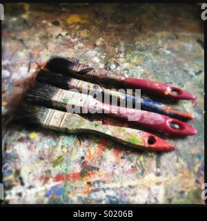 Paintbrushes on paint splattered table. Stock Photo