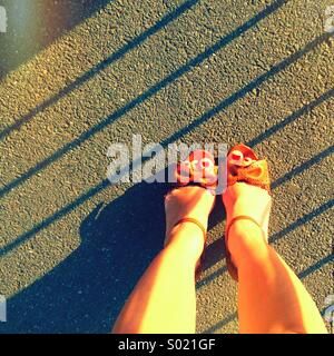 Girls shoes with red toenail polish - Stock Photo