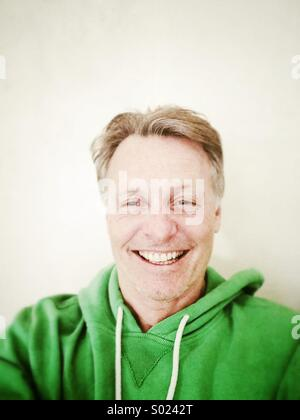 Happy smiling mature man in his forties wearing a green hooded top. - Stock Photo