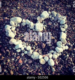A heart made of white stones and pebbles on a colourful beach - Stock Photo