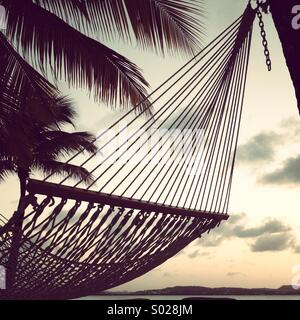Hammock on beach, at sunset, with palm trees. - Stock Photo