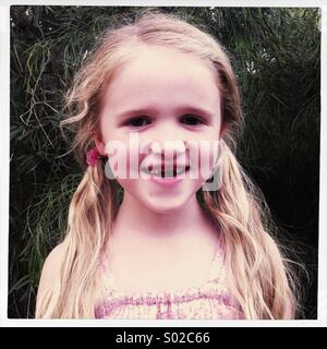 Little girl outside missing two front teeth - Stock Photo