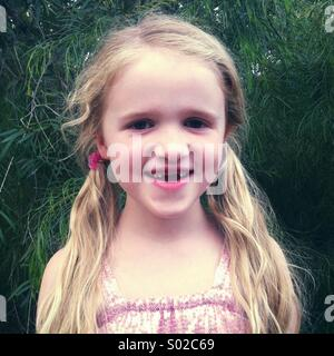 Little smiling girl missing two front teeth - Stock Photo