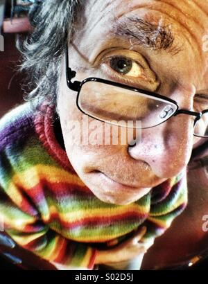 Raised eyebrow, face of mature Caucasian man wearing glasses, wide angle close up - Stock Photo