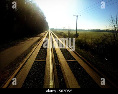 The guided busway tracks near Cambridge with the tracks leading to the vanishing point on the horizon - Stock Photo