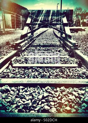 End of the line - railway tracks leading to buffers - Stock Photo