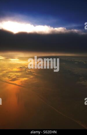 The East Coast of the United States from an airplane, with a beautiful sunset over the land and Atlantic Ocean. - Stock Photo